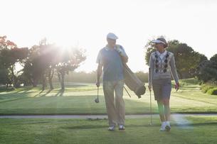 Golfing couple walking and chattingの素材 [FYI00002254]