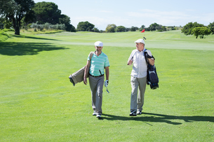 Golfer friends walking and holding their golf bagsの素材 [FYI00002260]