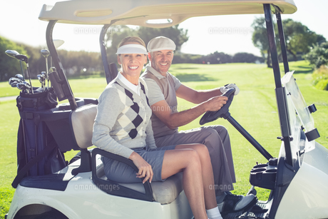 Happy golfing couple sitting in buggy smiling at cameraの素材 [FYI00002261]