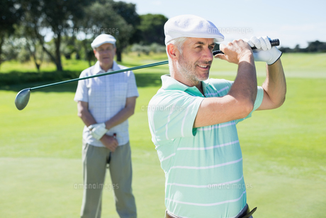 Golfer swinging his club with friend behind himの素材 [FYI00002265]