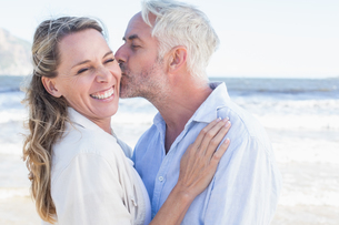 Man kissing his smiling partner on the cheek at the beachの写真素材 [FYI00002269]
