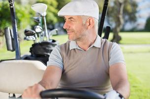 Happy golfer driving his golf buggyの素材 [FYI00002271]