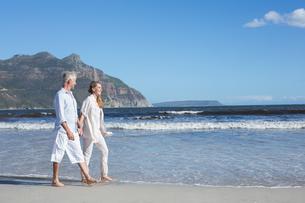 Happy couple walking barefoot on the beachの写真素材 [FYI00002273]