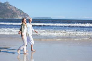 Happy couple strolling barefoot on the beachの写真素材 [FYI00002274]