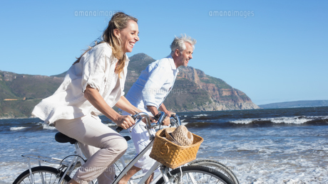 Smiling couple riding their bikes on the beachの写真素材 [FYI00002278]