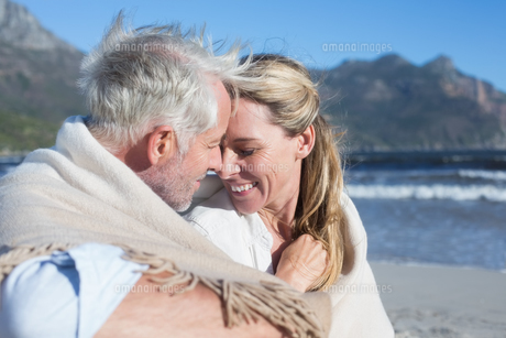 Smiling couple sitting on the beach under blanketの写真素材 [FYI00002280]
