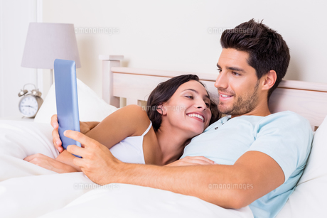 Attractive couple lying in bed with tablet pcの写真素材 [FYI00002299]