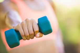 Fit woman exercising with dumbbells in the parkの写真素材 [FYI00002304]
