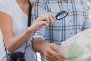 Young tourist couple using magnifying glass on the mapの写真素材 [FYI00002306]