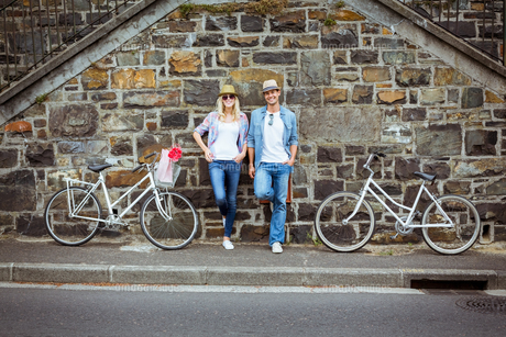 Hip young couple standing by brick wall with their bikesの写真素材 [FYI00002318]