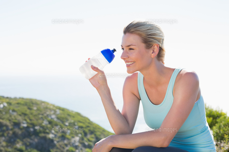 Fit blonde sitting at summit holding water bottleの写真素材 [FYI00002325]