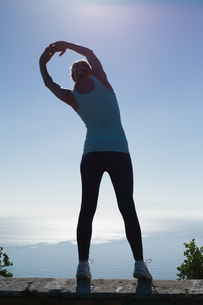 Fit woman stretching her arms looking out to seaの写真素材 [FYI00002331]