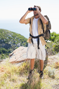 Handsome hiker looking through binocularsの素材 [FYI00002332]