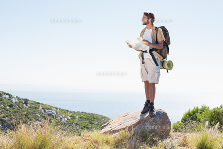 Handsome hiker holding map at mountain summitの写真素材 [FYI00002333]
