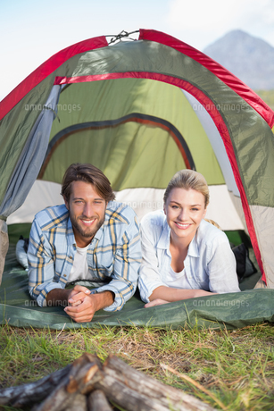 Attractive couple lying in their tent smiling at cameraの写真素材 [FYI00002342]