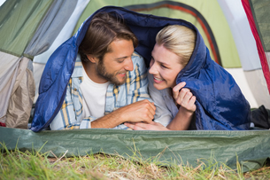 Attractive couple lying in their tent smiling at each otherの写真素材 [FYI00002343]