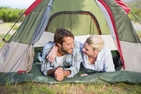 Attractive couple lying in their tent smiling at each otherの写真素材 [FYI00002347]
