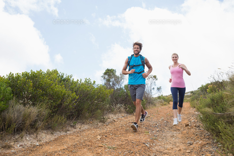 Fit attractive couple jogging down mountain trailの写真素材 [FYI00002348]