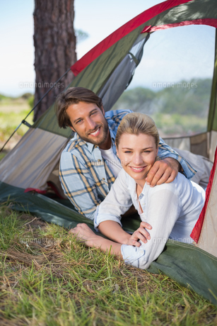 Attractive couple lying in their tent smiling at cameraの写真素材 [FYI00002349]