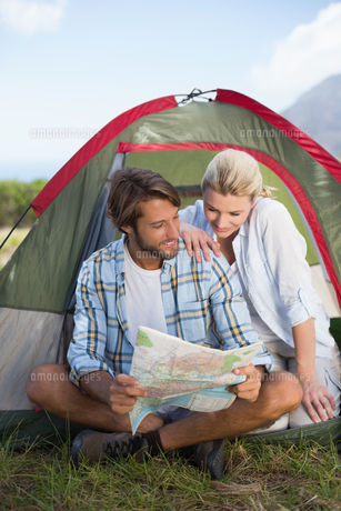 Attractive happy couple sitting by their tent reading mapの写真素材 [FYI00002350]
