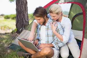Attractive couple sitting by their tent using laptopの写真素材 [FYI00002351]