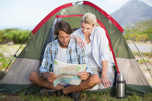 Attractive couple sitting by their tent reading mapの写真素材 [FYI00002352]