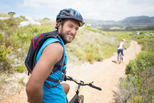 Fit couple cycling on mountain trail man smiling at cameraの写真素材 [FYI00002353]