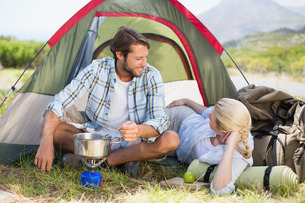 Attractive happy couple cooking on camping stoveの写真素材 [FYI00002356]