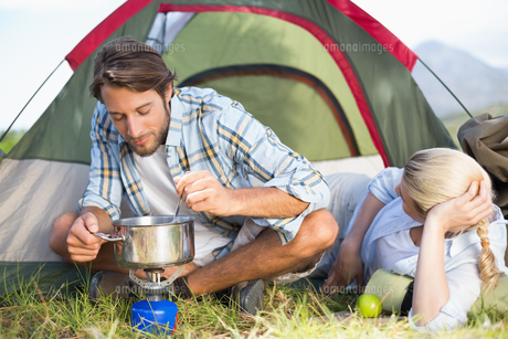 Attractive happy couple cooking on camping stoveの写真素材 [FYI00002357]