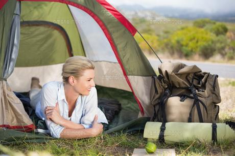 Attractive happy blonde lying in tentの写真素材 [FYI00002358]