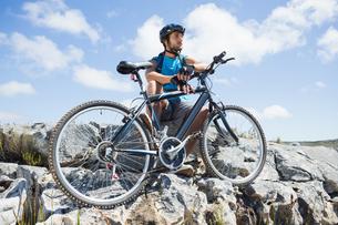 Fit cyclist taking a break on rocky peakの写真素材 [FYI00002359]