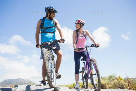 Fit cyclist couple taking a break on rocky peak smiling at each otherの写真素材 [FYI00002360]