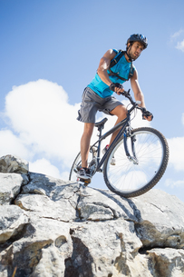 Fit man cycling on rocky terrainの写真素材 [FYI00002361]