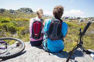 Fit cyclist couple taking a break on rocky peakの素材 [FYI00002363]