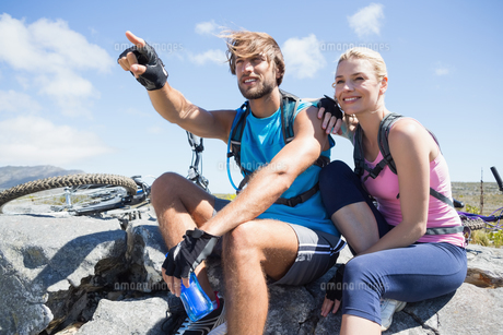Fit cyclist couple taking a break on rocky peakの写真素材 [FYI00002365]
