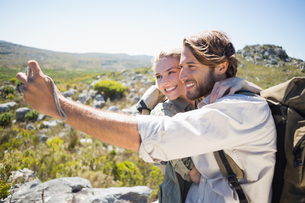 Hiking couple standing on mountain terrain taking a selfieの写真素材 [FYI00002381]