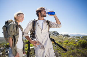 Hiking couple standing on mountain terrain taking a breakの写真素材 [FYI00002382]