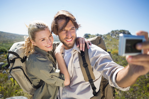 Hiking couple standing on mountain terrain taking a selfieの写真素材 [FYI00002383]