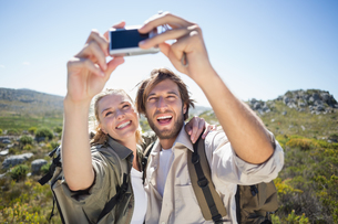 Hiking couple standing on mountain terrain taking a selfieの写真素材 [FYI00002384]