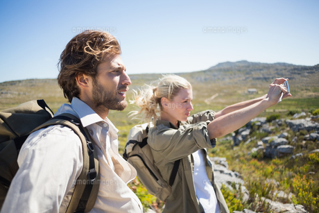 Hiking couple standing on mountain terrain taking a selfieの写真素材 [FYI00002386]