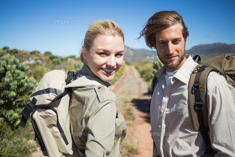Hiking couple walking on mountain terrain smiling at cameraの写真素材 [FYI00002387]