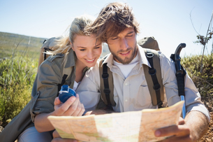 Hiking couple taking a break on mountain terrain using map and compassの素材 [FYI00002389]