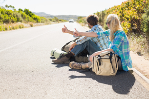 Attractive couple sitting on the road hitch hikingの写真素材 [FYI00002391]