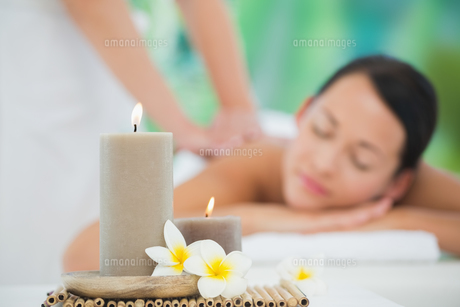 Beautiful brunette enjoying a back massage smiling at cameraの写真素材 [FYI00002405]