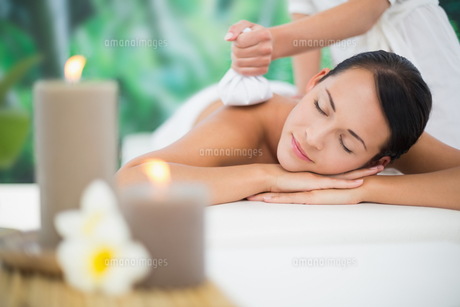 Beautiful brunette enjoying a herbal compress massageの素材 [FYI00002411]