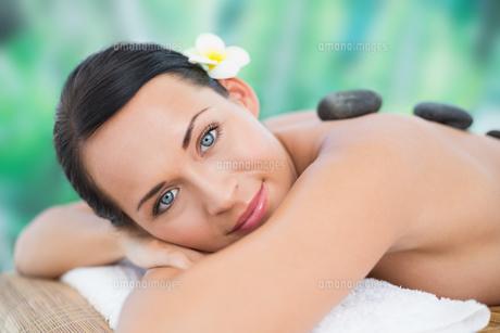 Beautiful brunette enjoying a hot stone massage smiling at cameraの写真素材 [FYI00002413]