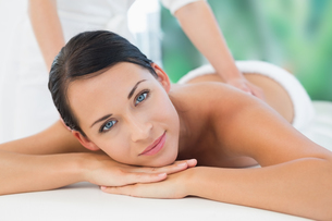 Beautiful brunette enjoying a back massage smiling at cameraの写真素材 [FYI00002419]