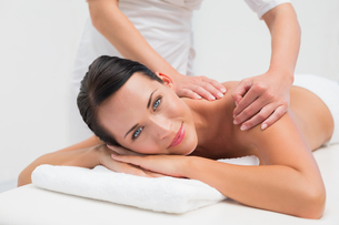 Beautiful brunette enjoying a back massage smiling at cameraの写真素材 [FYI00002423]