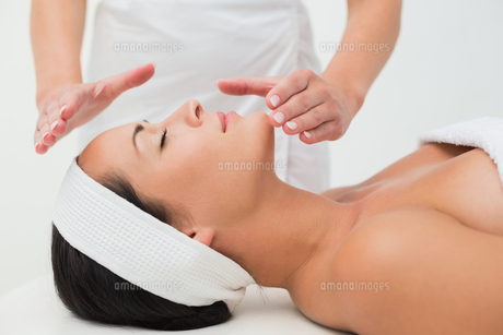 Peaceful brunette getting reiki therapyの写真素材 [FYI00002432]