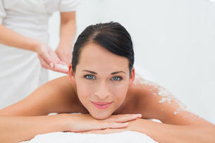 Peaceful brunette getting a salt scrub beauty treatmentの写真素材 [FYI00002436]